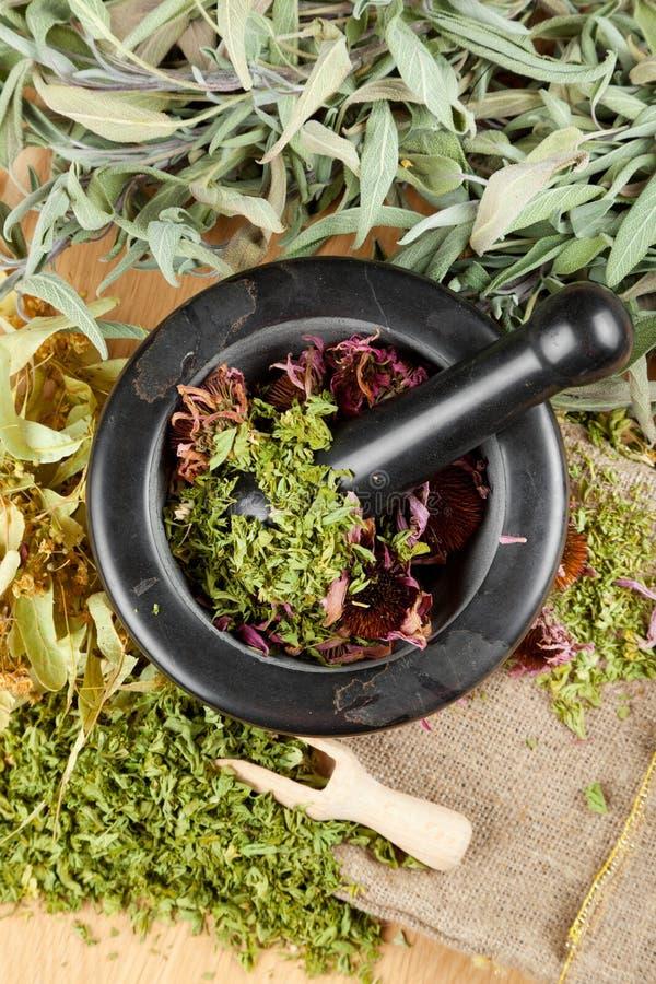 Излечивать травы на деревянных таблице, ступке и пестике стоковые фото
