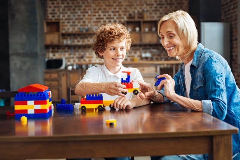 Излучающая бабушка помогая ее внуку с зданием автомобиля стоковое фото rf