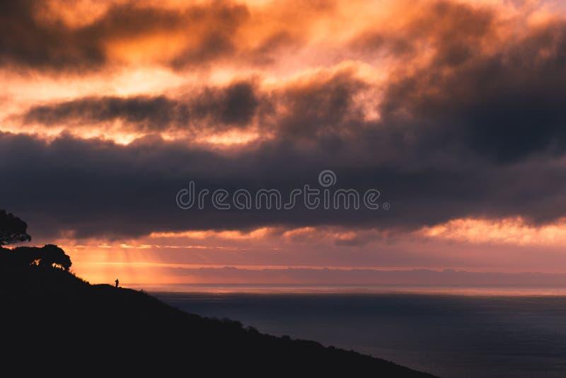Излучающий заход солнца с одиночным человеческим Silouette стоковое фото