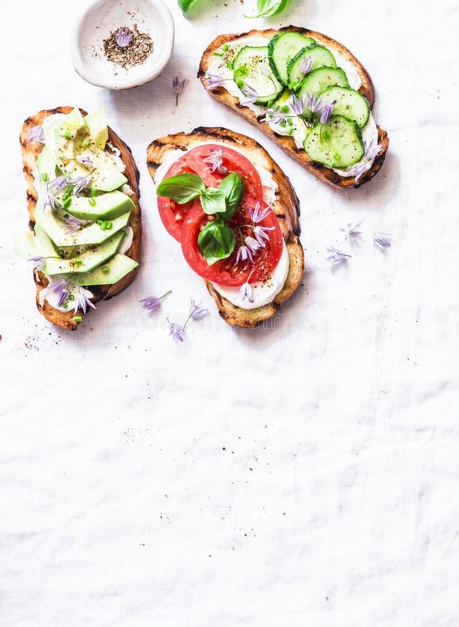 Изменения лета сандвичей - с плавленым сыром, авокадоом, томатом и огурцом на светлой предпосылке, взгляд сверху Здоровое питание стоковая фотография rf