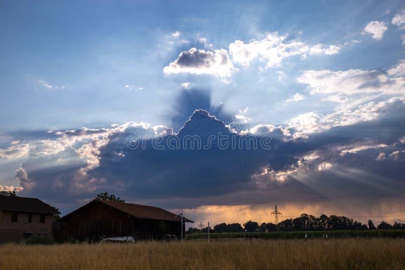 Изменяя погода с солнечными лучами над полем с хижиной, Германией стоковые изображения