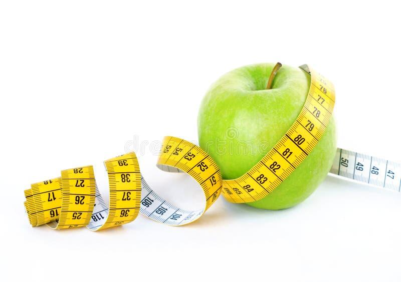Измеряя лента обернутая вокруг зеленого яблока стоковые изображения