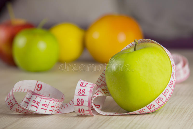 Измеряя лента обернутая вокруг яблока стоковое изображение rf