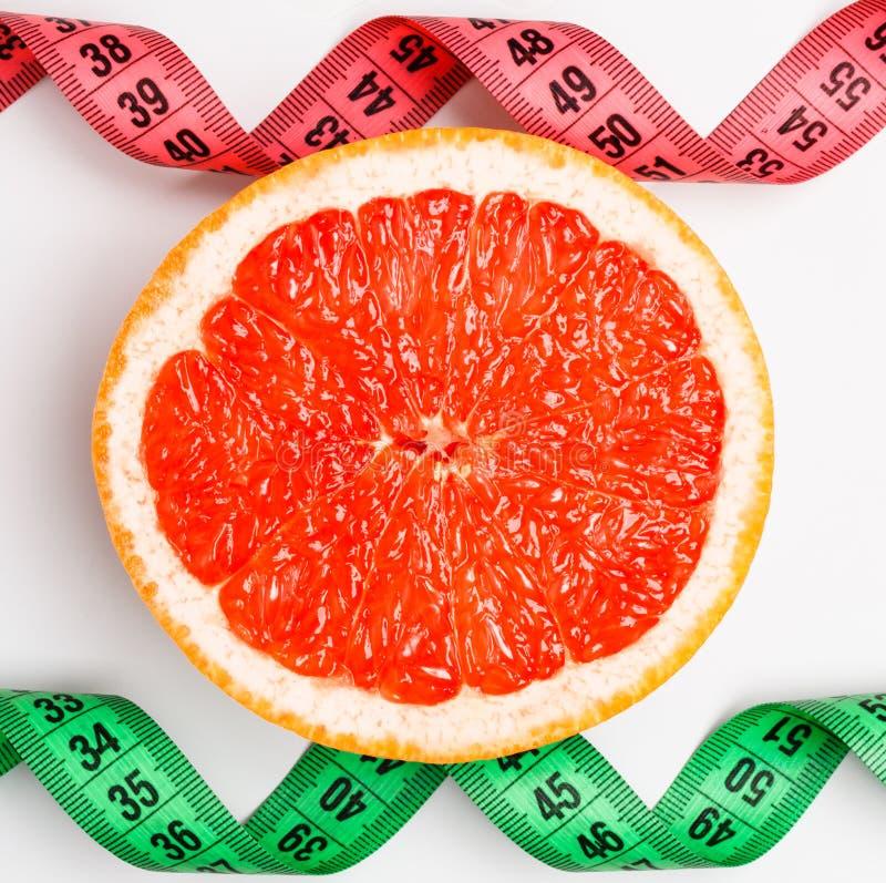 Измеряя ленты и кусок грейпфрута стоковые фото