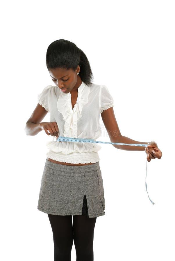 измеряя лента используя детенышей женщины стоковое изображение