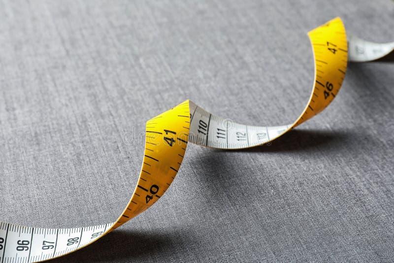 Измеряя лента на серой ткани стоковые изображения