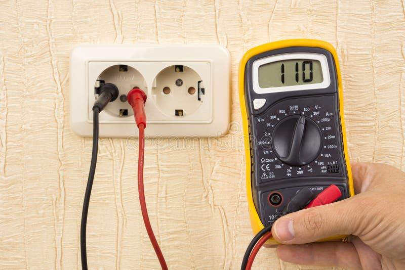 Измеряя напряжение тока с цифровым вольтамперомметром стоковые фото