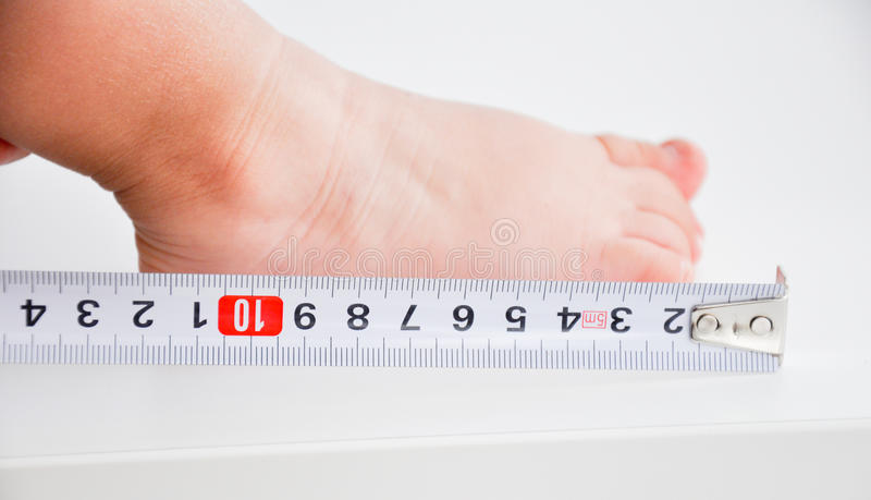Измеряя ноги младенца стоковое изображение