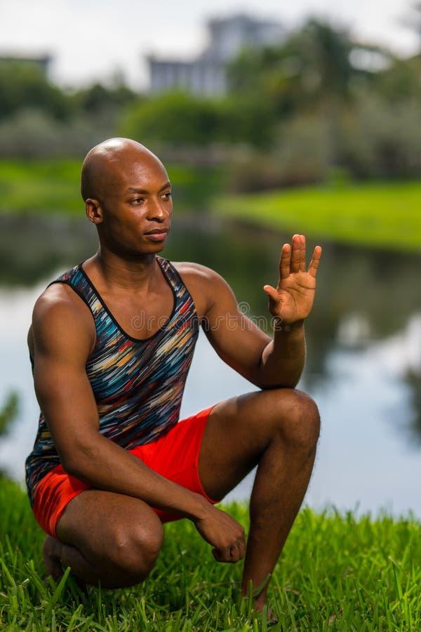 Изображение атлетического молодого Афро-американского человека сидя на корточках и развевая с камеры стоковое изображение