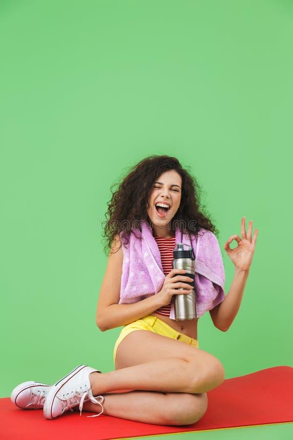Изображение атлетической девушки 20s в sportswear с полотенцем над шеей отдыхая и сидя на циновке фитнеса после разминки стоковые изображения rf