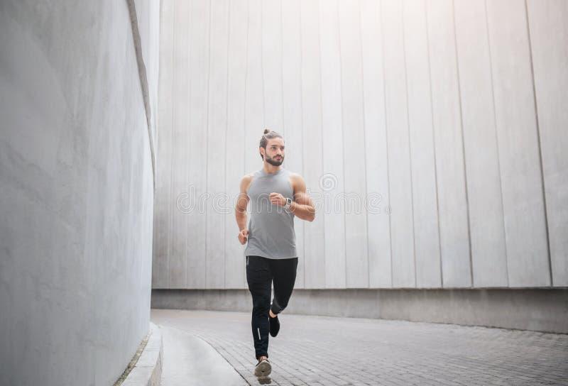 Изображение бегов jogger через конкретный коридор Он развевает с руками и взглядами для того чтобы выпрямить Серьезный молодой че стоковая фотография