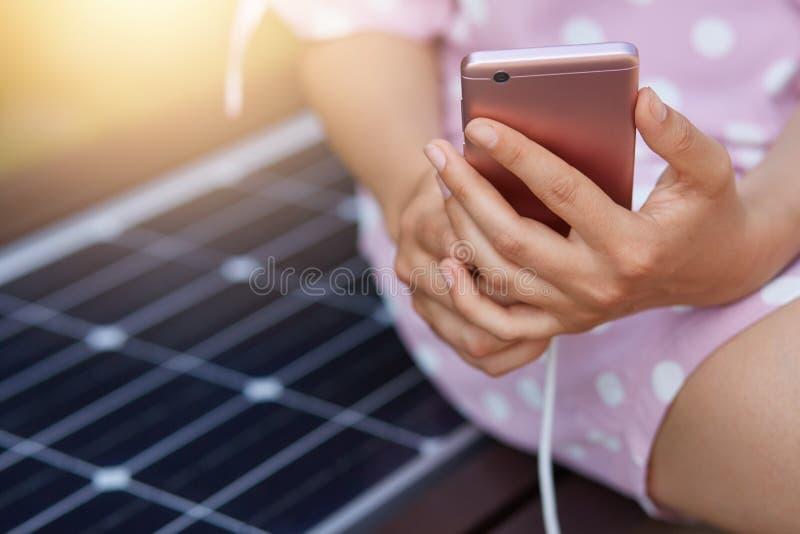 Изображение безликой женщины в розовом платье поручая ее умный телефон на свободном универсальном заряжателе панели солнечных бат стоковые изображения