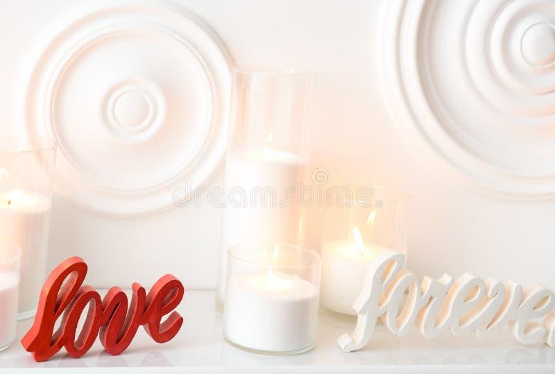 Изображение белого состава горящих свечей и влюбленности навсегда написанных в покрашенной древесине стоковая фотография rf