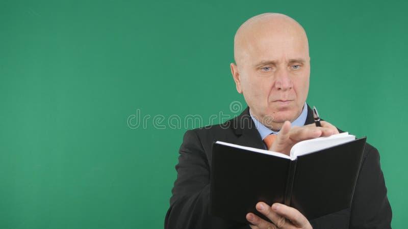 Изображение бизнесмена используя повестку дня с зеленой предпосылкой экрана стоковые фото
