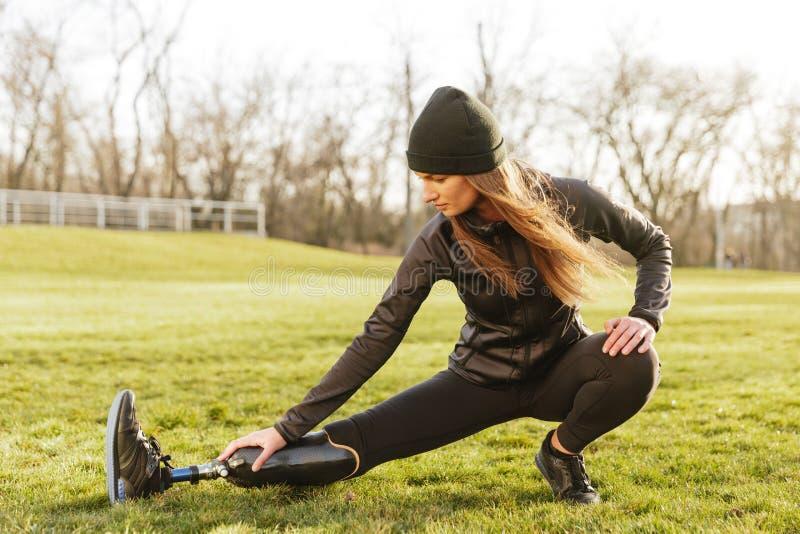 Изображение брюнет вывело атлетическую девушку из строя в sportswear, делая sp стоковое фото