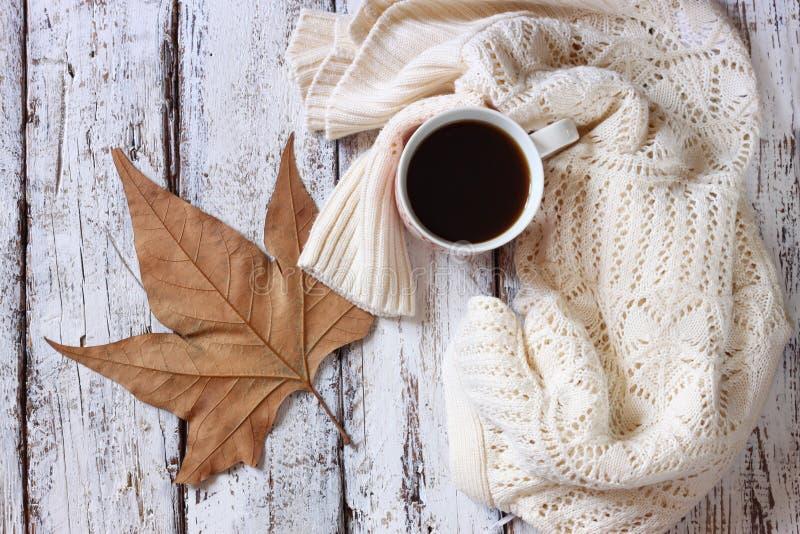 Изображение взгляд сверху белого уютного связанного свитера с к чашкой кофе и листьями осени на деревянном столе стоковое фото rf