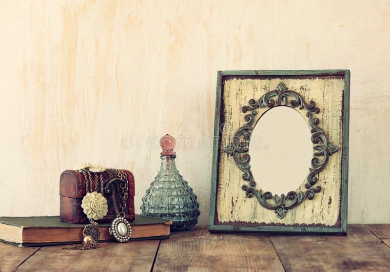 Изображение викторианских винтажных античных классических рамки, ювелирных изделий и флаконов духов на деревянном столе Фильтрова стоковая фотография rf