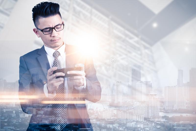 Изображение двойной экспозиции использования бизнесмена или smartphone или играют игру во время верхнего слоя восхода солнца с из стоковые изображения rf
