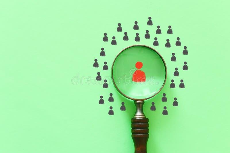Изображение дела лупы со значком людей над зеленой предпосылкой, строя сильную команду, человеческие ресурсы и управление стоковая фотография