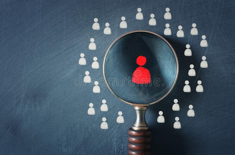 Изображение дела лупы со значком людей над предпосылкой доски, строя сильную команду, человеческие ресурсы и стоковое фото