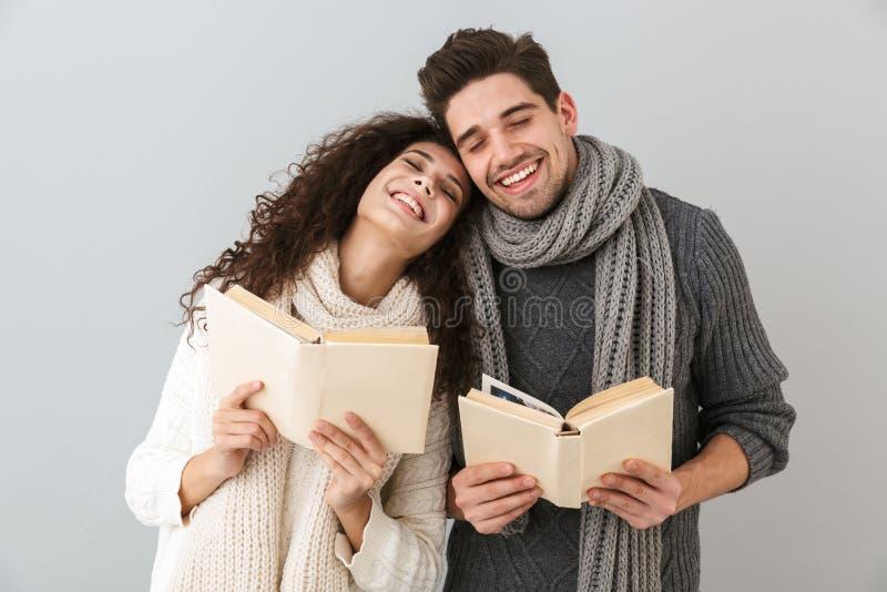 Изображение довольных книг чтения человека и женщины пар совместно, изолированное над серой предпосылкой стоковые фотографии rf