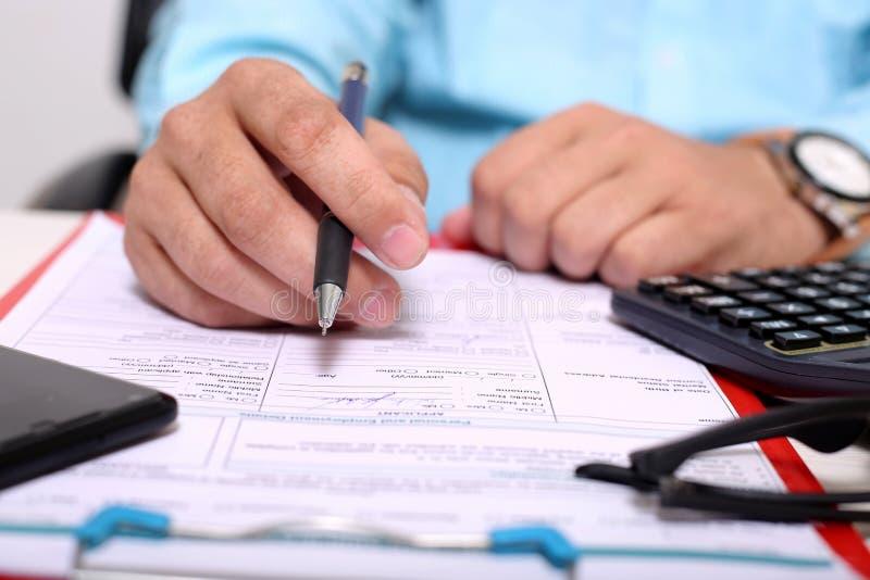 Изображение доски сзажимом для бумаги, формы, стекел, калькулятора, ручки и телефона Человек ручка удерживания в руке стоковое фото rf
