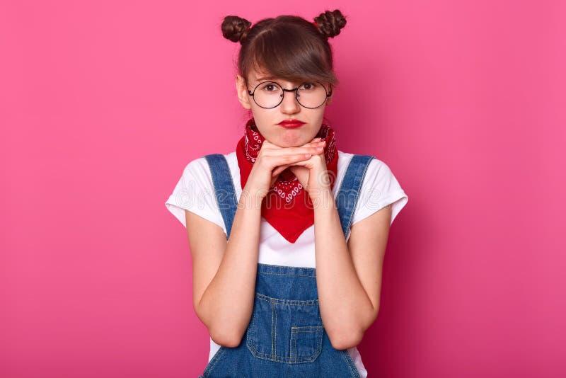 Изображение европейской расстроенной женщины с темными волосами и пуками, носит прозодежды, футболку и bandana Прелестная девушка стоковое изображение rf
