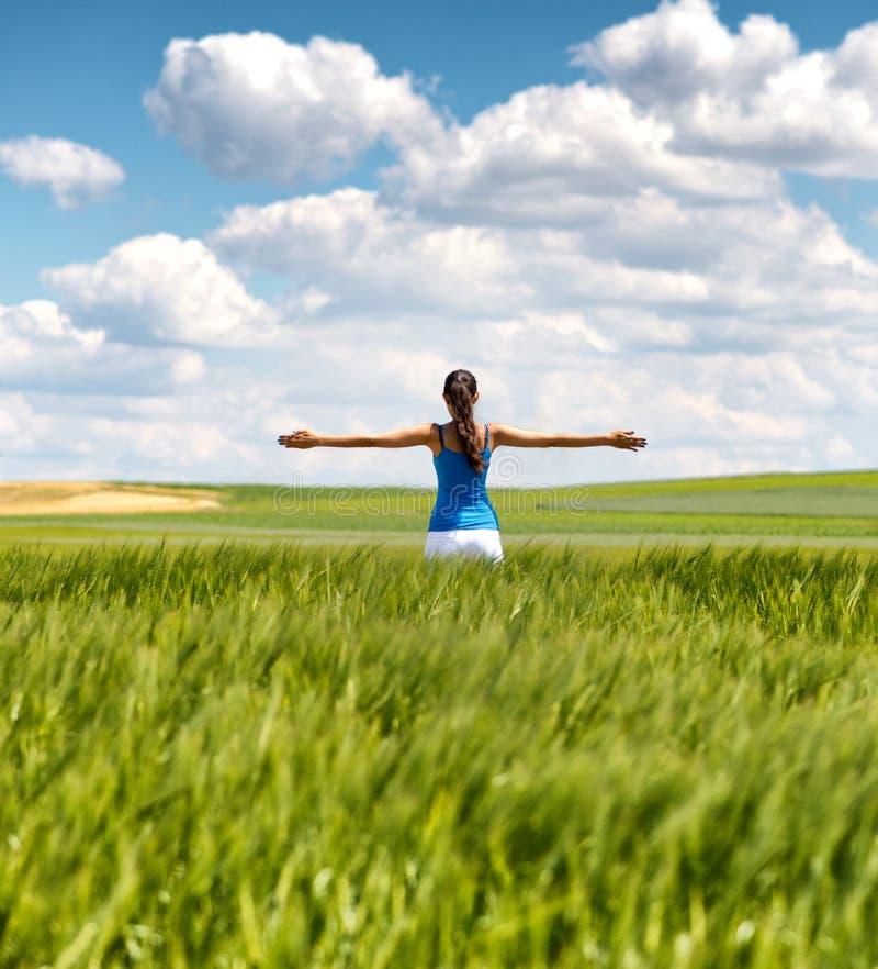 Изображение девушки в пшеничном поле с распространенными оружиями стоковое фото rf