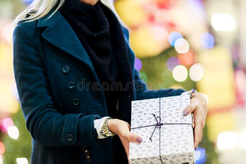 Изображение женщины в пальто с подарочной коробкой на предпосылке рождественской елки стоковая фотография