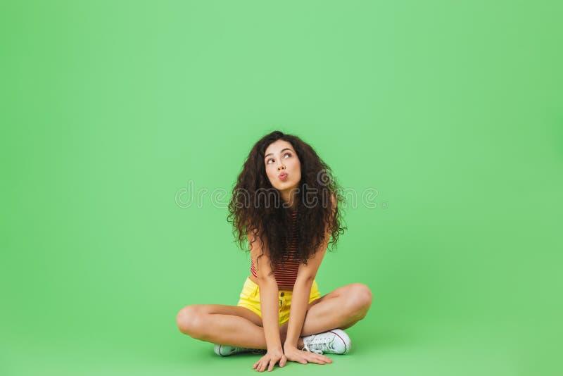 Изображение женщины 20s брюнета радуясь и усмехаясь пока сидеть на поле с ногами пересекл стоковое изображение