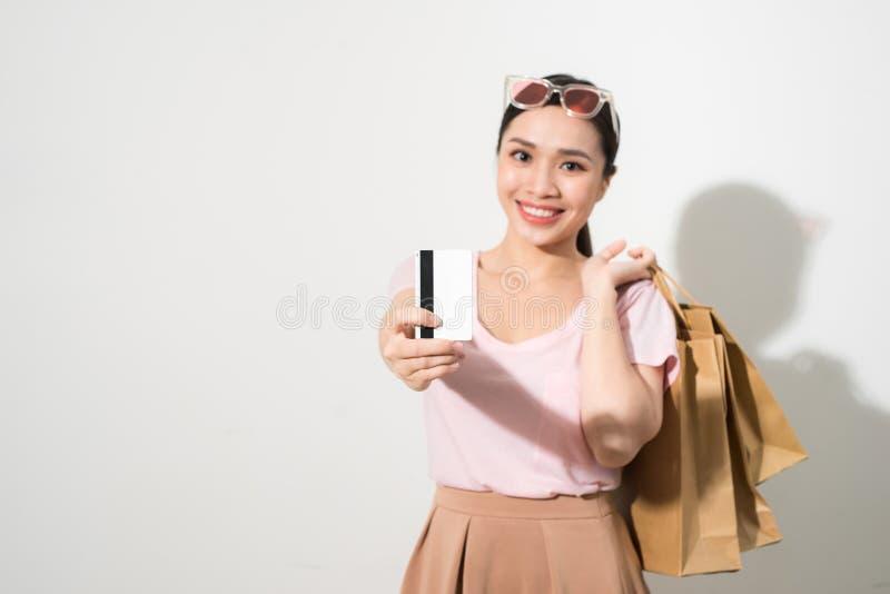 Изображение жизнерадостного положения молодой женщины изолированного над белой предпосылкой держа хозяйственные сумки и кредитную стоковое изображение