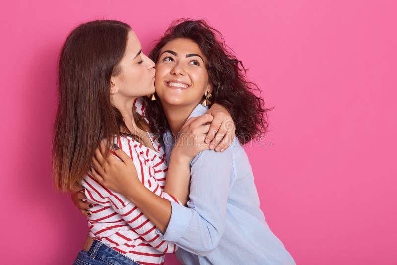 Изображение 2 жизнерадостных маленьких девочек в ярких одеждах обнимая и целуя на щеке, изолированное на румяной предпосылке стен стоковая фотография