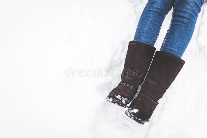 Изображение зимы ног в ботинках на снеге, снеге, девушка сидит, для того чтобы ввести текст, стоковые изображения rf