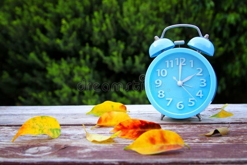 Изображение изменения времени осени Понижается назад концепция Высушите листья и винтажный будильник на деревянном столе outdoors стоковая фотография