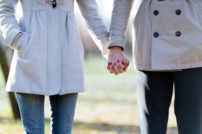 Изображение конца-вверх любящих пар держа руки пока идущ стоковая фотография rf