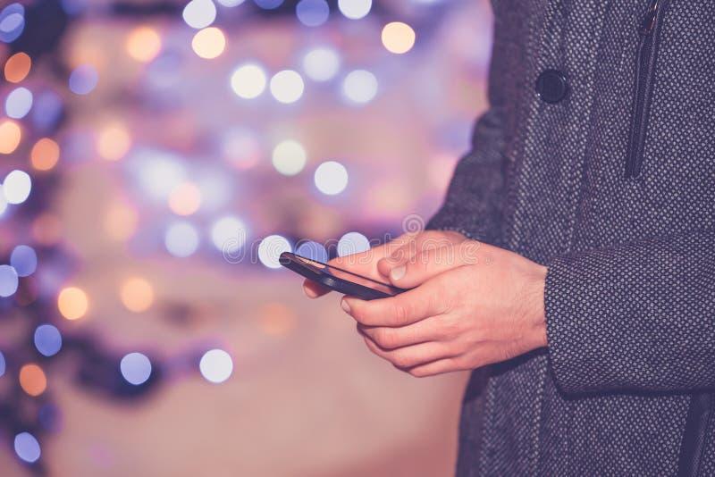 Изображение конца-вверх мужских рук используя смартфон вечером стоковое изображение rf