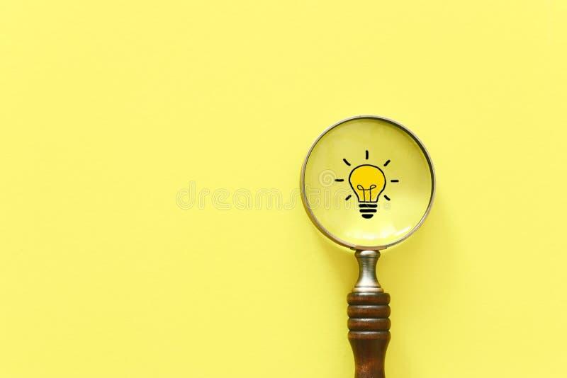 Изображение концепции дела Лупа и лампа Обнаружение самых лучших идеи и воодушевленности среди других стоковые изображения