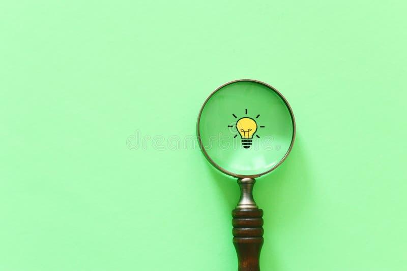 Изображение концепции дела Лупа и лампа Обнаружение самых лучших идеи и воодушевленности среди других стоковое фото