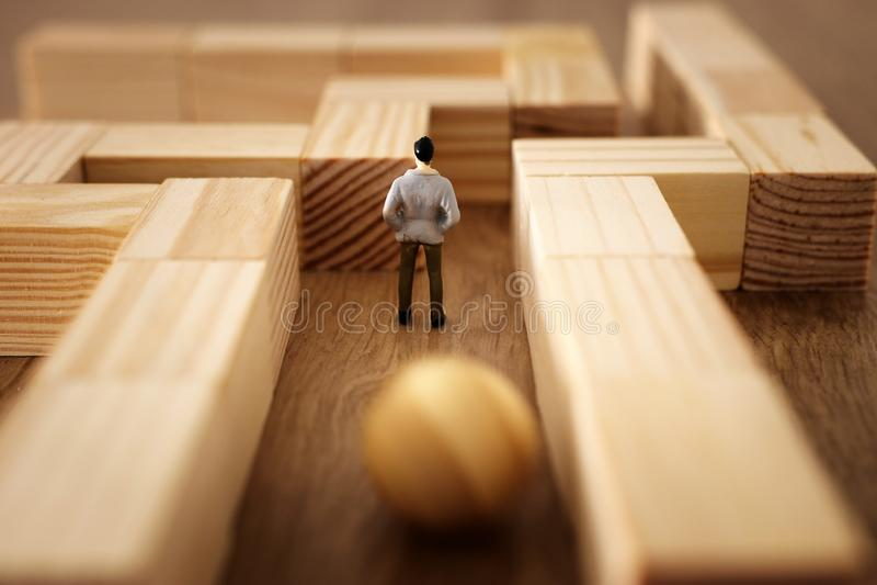 Изображение концепции дела проблемы Человек стоит в лабиринте ища выход и незнающий опасности причаливая ему стоковое изображение
