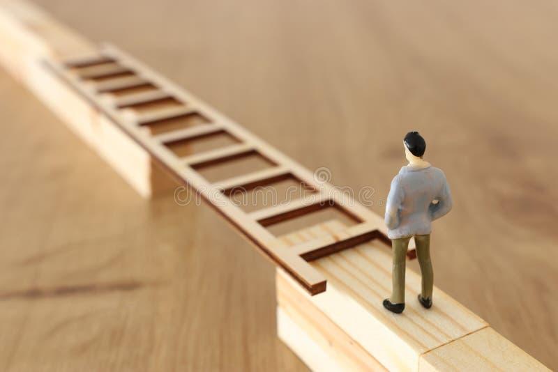 Изображение концепции дела проблемы Человек стоит на краю высокой стены и проходит зазор путем устанавливать лестницу Проблема стоковые изображения