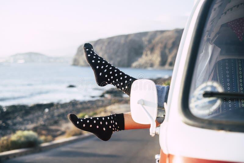 Изображение концепции свободы и счастья с парами женских ног из окна классического фургона припаркованного около вида на океан по стоковое изображение
