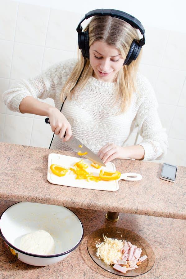 Изображение красивой белокурой жизнерадостной молодой женщины с наушниками слушая к музыке делая портрет пиццы стоковая фотография