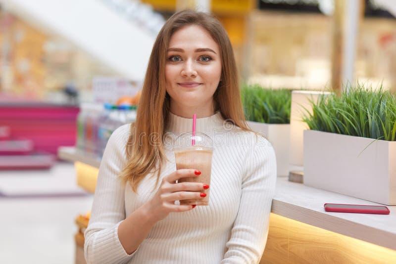 Изображение красивой молодой женщины сидит в кафе с коктейлем, смотрит усмехающся на camere, имеет длинные волосы bonde, одело бе стоковые изображения rf