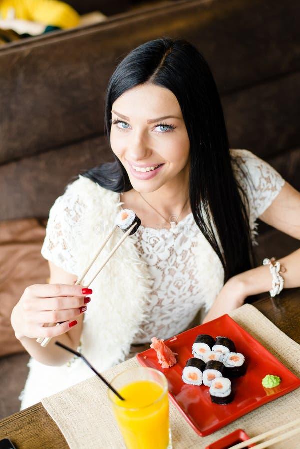 Изображение красивой молодой женщины брюнет есть вкусные суши имея сидеть потехи счастливый усмехаясь в ресторане & смотреть каме стоковые фото