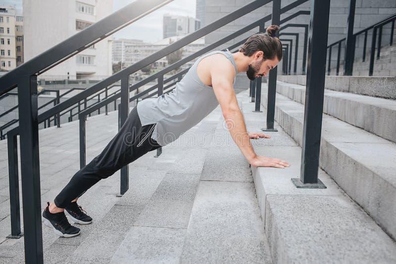Изображение крепкого спортсмена работая на шагах Он стоит в положении планки и смотрит вниз Гай спокойно и стоковые изображения
