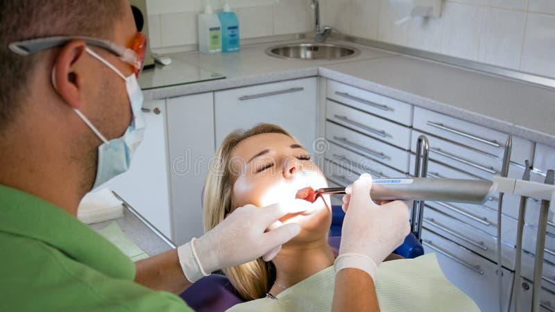 Изображение крупного плана дантиста используя photopolymer и УЛЬТРАФИОЛЕТОВОЙ лампы для обработки зубов стоковые фото