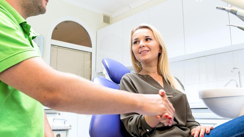 Изображение крупного плана дантиста тряся руки при усмехаясь молодая женщина сидя в стуле дантиста стоковые фото