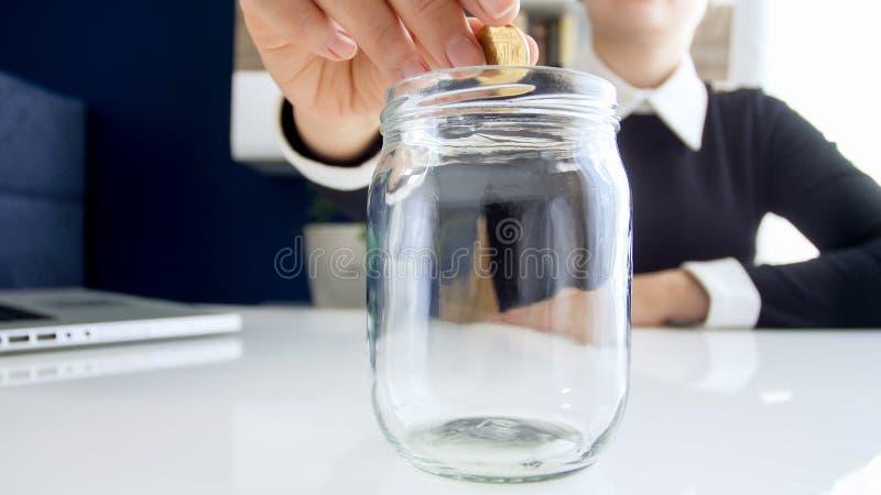 Изображение крупного плана коммерсантки кладя одну золотую монетку в стеклянный опарник с сбережениями стоковое изображение
