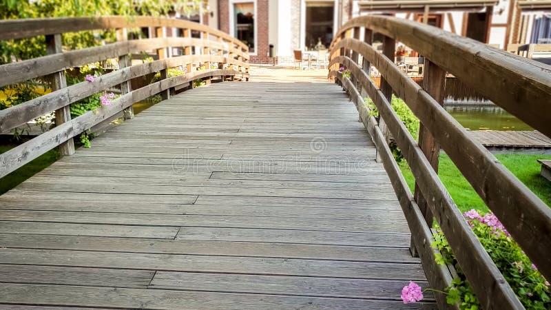 Изображение крупного плана красивого старого деревянного моста через небольшое спокойное реку в старом европейском городке стоковое фото rf