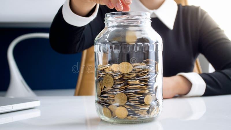 Изображение крупного плана монеток молодой коммерсантки бросая в стеклянном опарнике с сбережениями стоковые изображения
